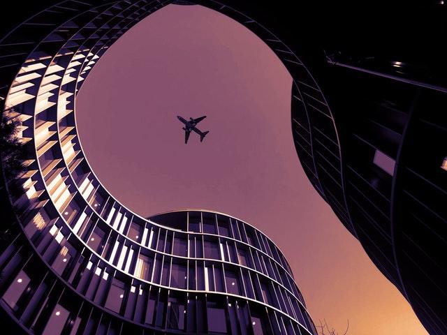 Lietadlo v oblakoch medzi budovami.jpg