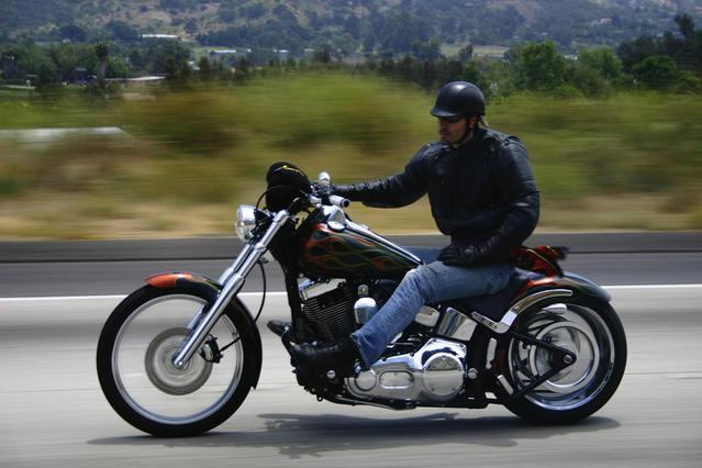 Motorkár ide po ceste, čierna bunda, rifle, otvorená prilba