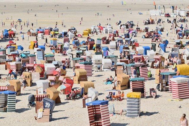 Pláž plná turistov, slnečníkov a stanov.jpg