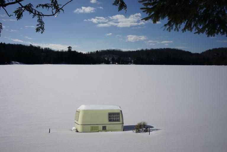 Malý mobilný dom postavený na zasneženej rovine.jpg