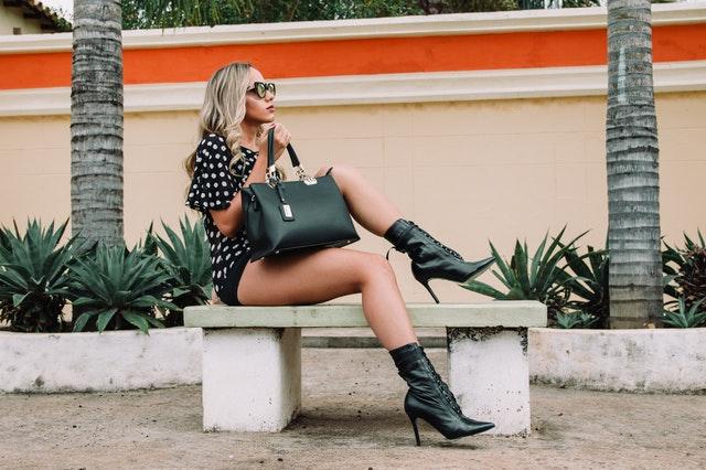 Žena v bodkovaných šatách na vysokých podpätkoch sedí na lavičke.jpg