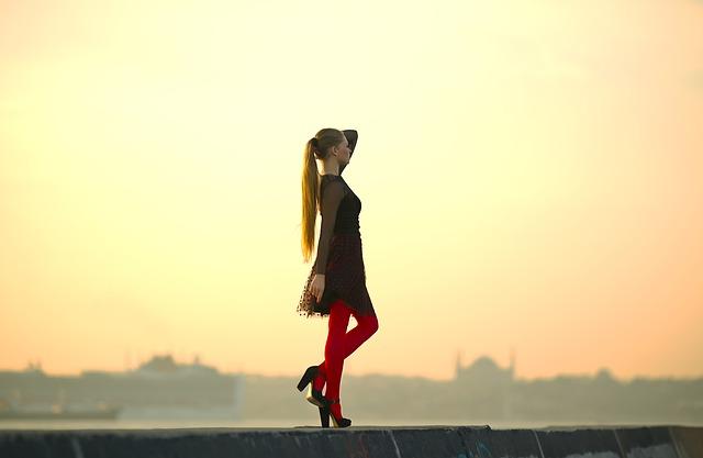 Žena v čiernych šatách a červených silónkach v topánkach na podpätku.jpg
