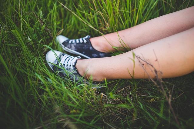 Ženské holé nohy v teniskách, v tráve.jpg